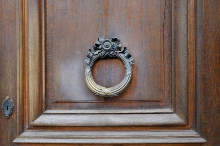 Metal antique door knocker on wooden door