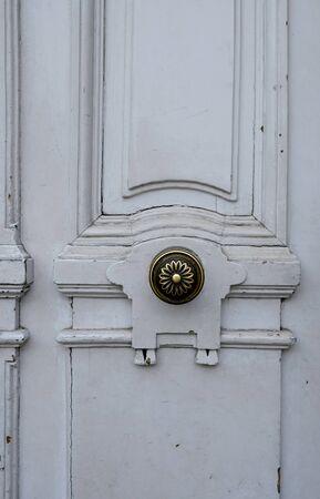 Old metal door knob on white wooden door.