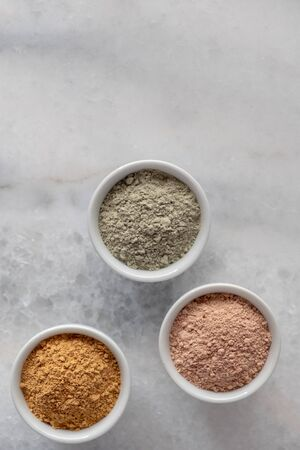 Set of different cosmetic clay mud powders on white background