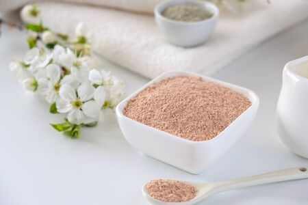 Ceramic bowl with red clay powder, ingredients for homemade facial and body mask or scrub and fresh sprig of flowering cherry on white background. Spa and bodycare concept.