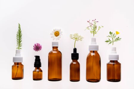 Wild flowers and medicine glass bottle on white background is used for cosmetic skin care product. Concept of natural cosmetics or alternative medicine