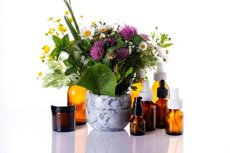 Wild flowers in a marble mortar and medicine glass bottle with essential oil, cosmetic oils, aromatherapy, phytotherapy, alternative medicine, natural skin care. Stock fotó