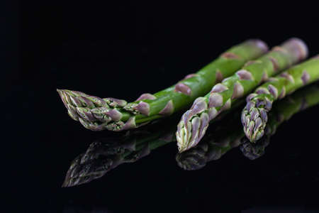Fresh organic green asparagus isolated on black background. closeup shot