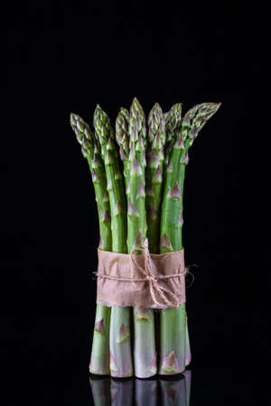 Asparagus. Bunch of fresh green asparagus tied on black background.