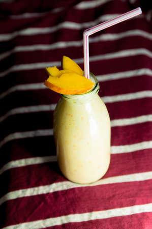 Milk shake with mango on stripy background. photo