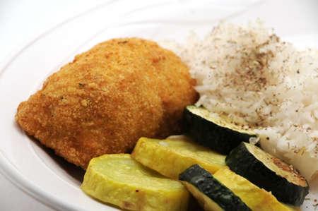 sautee: pollo Kiev e da squash e di riso saltati su una piastra bianca
