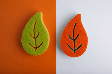 Flat lay with colorful leaf shaped sponges for home and dishes cleaning on orange and white background
