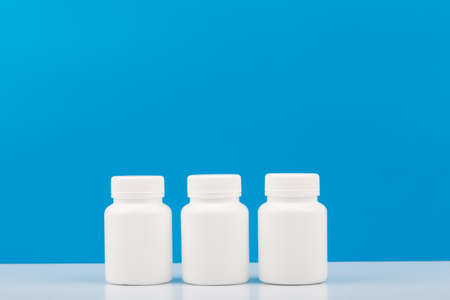 Three white medication bottles against blue background. Concept of vitamins, supplements, medication and healthcare