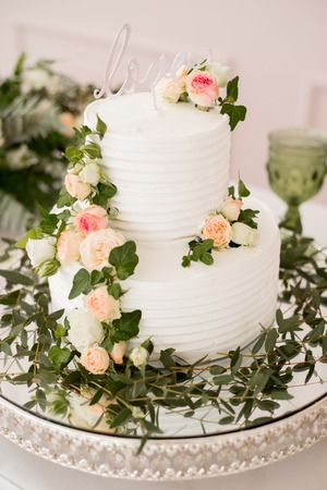 beautiful decorate table with candles, vase with flowers and wedding cake on the table