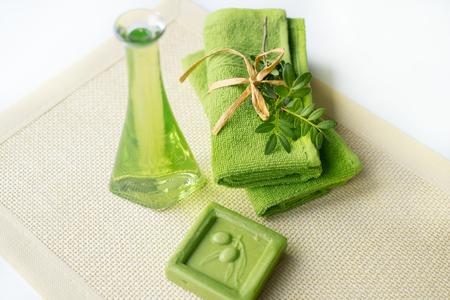 Spa kit: liquid soap, sea salt, green towel, fresh flowers, olive leaves on an old yellow napkin Stock Photo