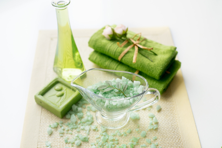 Spa kit: liquid soap, sea salt, green towel, fresh flowers, olive leaves on an old yellow napkin Stock Photo