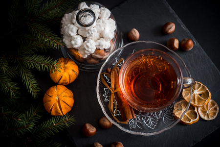 Sweet winter holidays background with various cookies and cup of hot spicy black tea on dark rustic table with copy space.