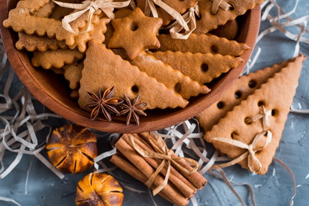 Christmas spices, gingerbread cookies and baking ingredients on grey concrete background. Cinnamon, anise stars, nutmeg, cardamon, cloves, brown sugar for Christmas cookies.
