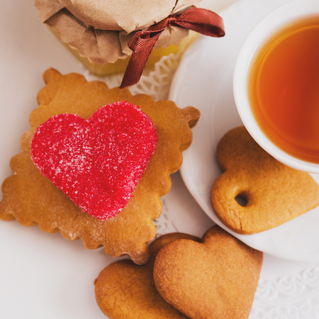 tea cup with heart shaped biscuits. Sugar red biscuits. Gingerbread spices with spices in the form of heart. A square, equal sides. Instaphoto with filters Stock Photo