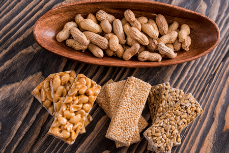 Snacks - mix of energy bars with peanut, sesame and sunflower seeds on a wooden background. Nuts in caramel, honey Snack food. Unhealthy eating or a healthy