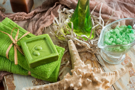 Vintage green spa still life with handmade soap, Scented candles on a vintage textured wooden background