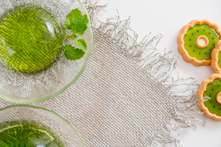 Green jelly with mint leaves in glass on wooden background. Juice with ice in gelatin. on a linen napkin on a white background. Top view. Copy the space