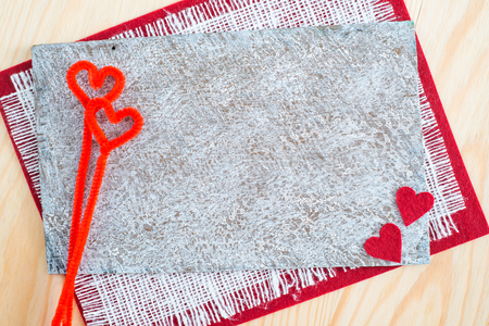 Greeting card with red ribbon and a key on canvas background for Valentine's day, On a wooden table