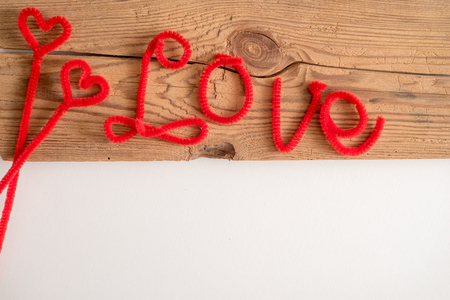 Love is a word is written spelling font. The word love red. White background, wooden table. Copy space. Place for your inscription Foto de archivo