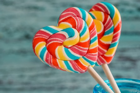 Two colored striped rainbow candy on a stick in the form of a heart. on a blue green old vintage wooden background. The concept for Valentines Day.