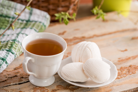 Beautiful composition with cup of tea and marshmallow. Spring Breakfast. A cup of tea with a white marshmallow on a wooden background. Sprigs of a tree green buds and leaves.