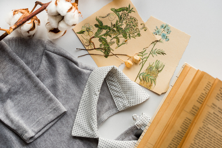 Spring composition. Cotton flowers, card drawing greeting card with flowers. An old book with yellow pages. The jacket blouse with collar of gray color. herbarium on a white background. Top wiew Stock Photo