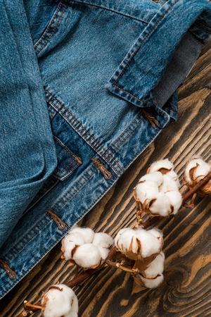 Details denim jacket, dried cotton flowers blue back jacket jeans texture-wooden background