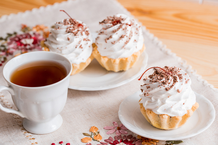 Vanilla cupcakes on white wood background, cup of tea, a spring breakfast
