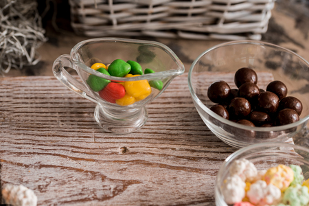 Frame of colorful bright assorted candy in bowls and jars, candy canes and rainbow colored lollipops on black with scattered candy hearts and jellybeans around a central copy space on slate