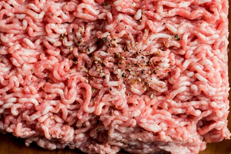 minced pork, Minced meat texture close up - top view minced meat raw fresh macro. Close-up with pepper, salt spices. cooking cutlets. Stock Photo