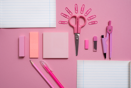 On pink background, school accessories and a pen, colored pencils, a pair of compasses, a pair of compasses, a pair of scissors. Copy space, top view