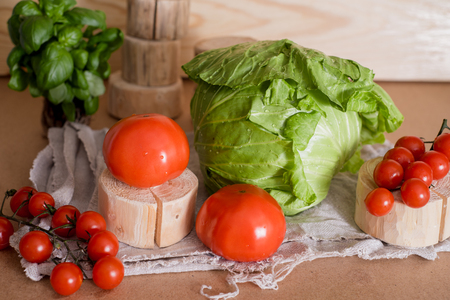 Tomatoes are large and cherry on a branch. Cabbage cabbage. On a wooden board, stand. Fresh basil. On a linen mint linen old napkin. Preparation of salad. Healthy Eating
