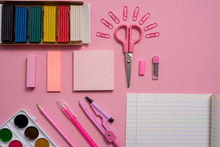 Stationary concept, Flat Lay top view Photo of Scissorsschool supplies, notepad and pens, color pencils, on a pink background. pink background with copy space. Stock Photo