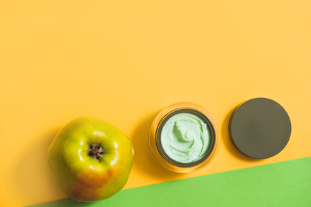 a face cream, a green apple, a yellow daisy on a bright background.Natural cosmetics with fresh flowers in an open jar