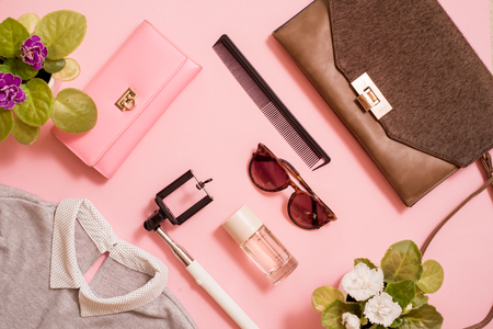 clothes, a purse and a bag, a comb and sunglasses, a self-stick and eau de toilette. Flowers are next to a pink background. Fashion trends of summer for the women. Flat lay, top view. Copy space Archivio Fotografico