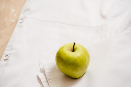 an apple lies on a white medical dressing gown. Stock Photo