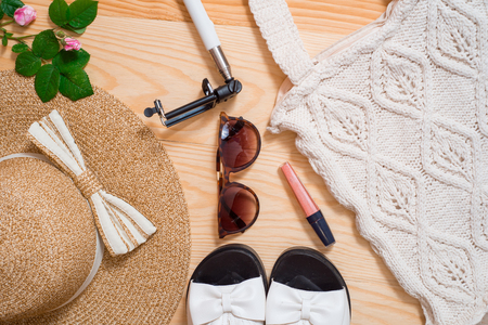 Colorful summer female fashion outfit flat lay. Straw hat, bamboo bag, stick for selfie, sunglasses, top view, copy space, wide composition. Summer fashion, holiday.