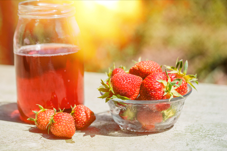 Fresh strawberry drink on wood background, outdoor a sunny summer day Stock Photo