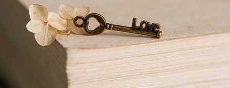Closed book, the key symbol of Valentine's Day. Vintage old heart. On a textured blue green background with cracked colors of crockeler.Long wide banner.