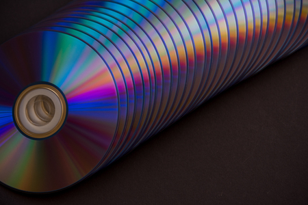 sd and dvd disks on a dark background. large stack