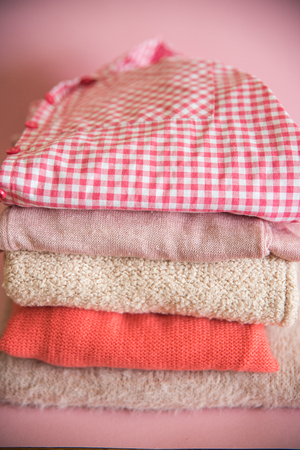 Pile of clothes on table. pink and purple shirts and a knitted sweater. Stockfoto