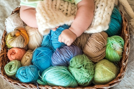 A cute baby lies on a basket with tangles of knitting threads. Hendmeid of multi-colored threads. Children's hands Фото со стока