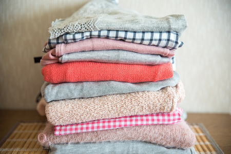 Pile of clothes on table. pink and purple shirts and a knitted sweater. Stock Photo