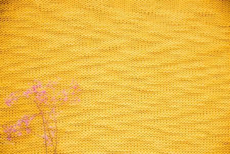 Knitted fabric textured background. yellow clothes and purple dried flowers. autumn concept