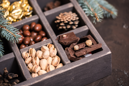 Christmas composition on a dark background. Decorative wooden box with Nuts, candies in a golden wrapper, pieces of chocolate, cones and centuries of spruce