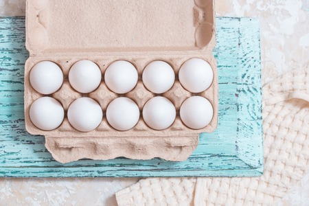 Mix of chicken egg and duck egg put on paper tray, on blue wooden vintage background. Linen cloth. Cooking food. Flat lay