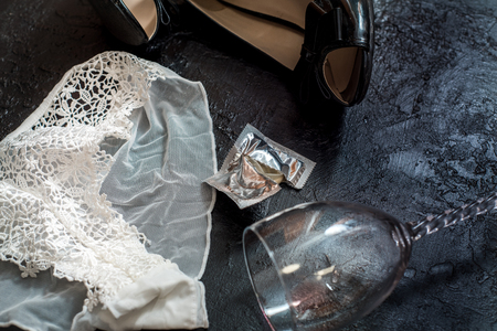 Sexy white lingerie, wine in a glass, black patent leather shoes, open condom after sex or after a stormy night Banco de Imagens
