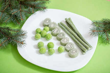 Christmas green sweets, candies on a plate, a branch of spruce on a green