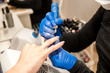 Nail tech filing nails with nail file. Professional manicure tools. Blue gloves on the hands of the master
