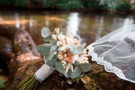 Beautiful bridal bouquet, stream in the forest. natural nature. white veil on a stone with moss.